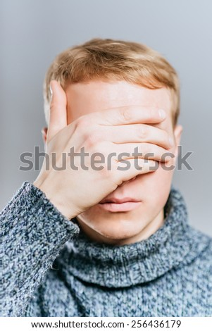 Closeup of young man hiding face whit hands - stock photo