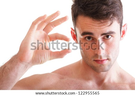 Closeup of young man holding pills isolated on white - stock photo