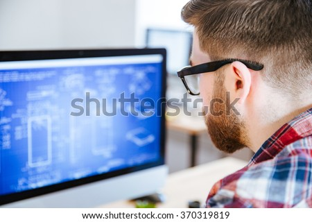 Closeup of young man in glasses with beard making blueprints on computer - stock photo