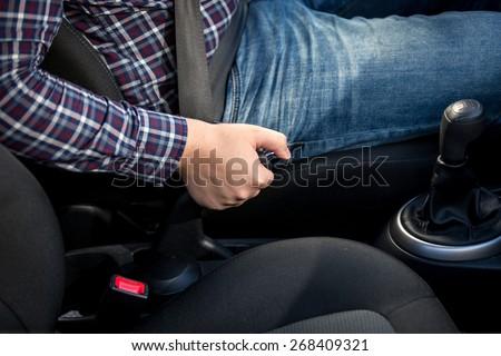 Closeup of young man pulling handbrake lever in car - stock photo