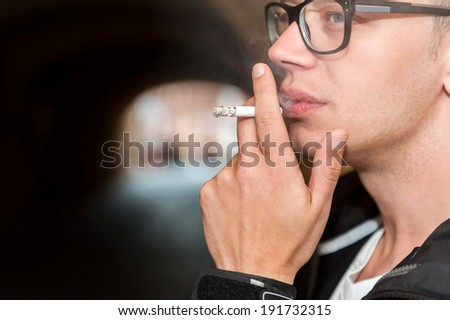 Closeup of young man smoking a cigarette in the street in a tunnel. - stock photo
