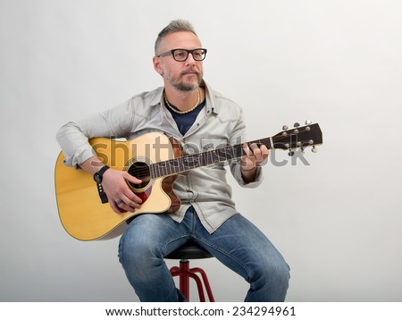 Closeup of young man with black glasses practicing and playng guitar. Studio portrait in gray background - stock photo