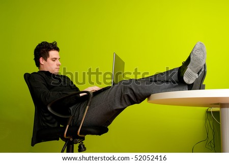 Closeup of young man working on laptop with legs on the table - stock photo