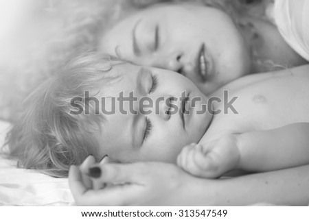 Closeup of young pretty loving mother with soft curly hair embracing small tiny cute male lovely baby sleeping indoor in bed with white linen black and white, horizontal picture