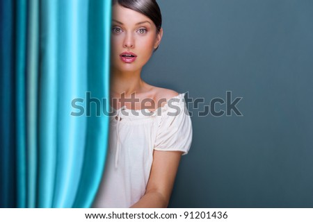 Closeup of young, pretty woman standing near curtain and holding it. Lots of copyspace for your text and logo - stock photo