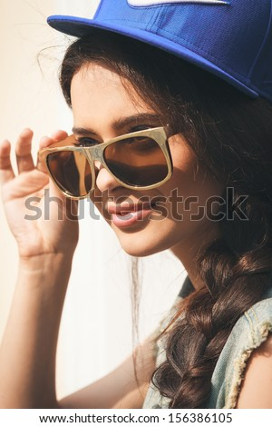 Closeup of Young sexy woman in blue cap and jeans jacket  looking away through golden sunglasses .  Outdoors, lifestyle. - stock photo