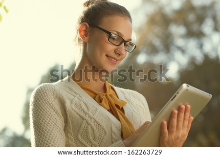 Closeup of young smart woman with tablet outdoors. Distance education. - stock photo
