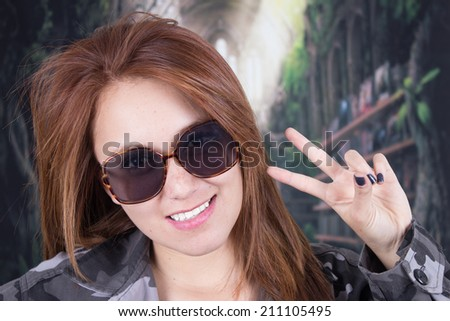 Closeup of young smiling girl wearing military uniform and sunglasses gesturing peace sign - stock photo