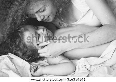 Closeup of young smiling loving mother with soft curly hair touching with hand small tiny cute male lovely baby sleeping indoor in bed with white linen black and white, horizontal picture - stock photo