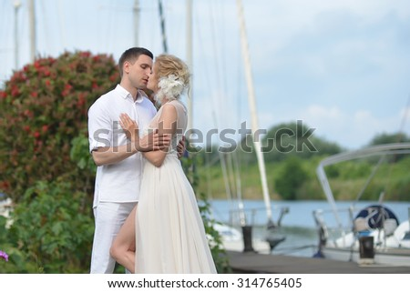 Closeup of young wedding couple of man in shirt and woman in long white dress and flower in blonde hair embracing and kissing standing in harbour outdoor on natural background, horizontal picture
