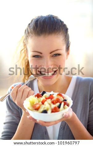 Closeup of young woman eating healthy food