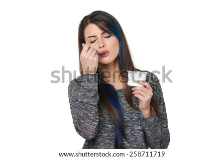 Closeup of young woman enjoying  taste of yoghurt with closed eyes, isolated on white