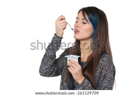 Closeup of young woman enjoying  taste of yoghurt with closed eyes, isolated on white - stock photo
