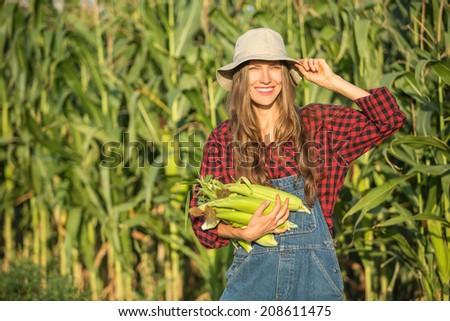 Closeup of young woman farmer at corn harvest - stock photo