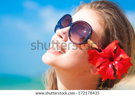 closeup of young woman in sunglasses smiling on beach - stock photo