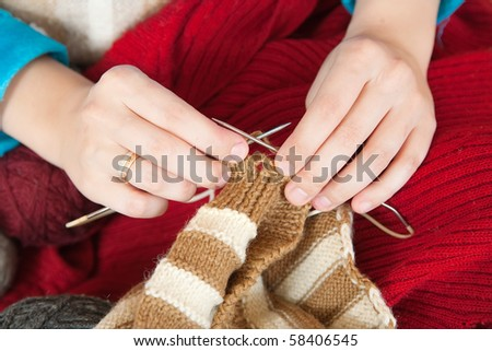 Closeup of young woman knitting with knitting-needle at home - stock photo