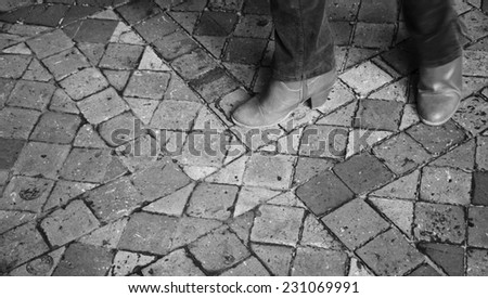 Closeup of young woman legs in motion on terracotta tile floor in old house. Aged photo. Black and white. - stock photo