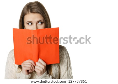 Closeup of young woman peeking over the edge of the opened book, looking to the side at blank copy space, over white background - stock photo