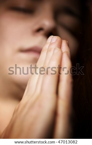 Closeup of young woman praying with folded hands and closed eyes - stock photo