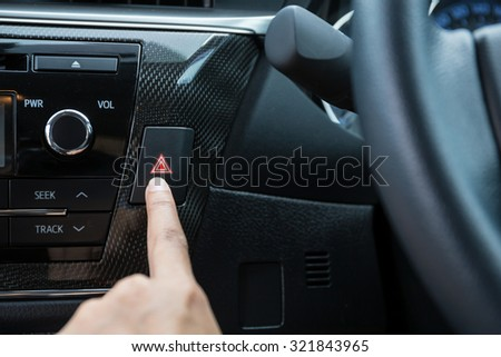 Closeup of young woman pressing emergency button on car sport dashboard. - stock photo