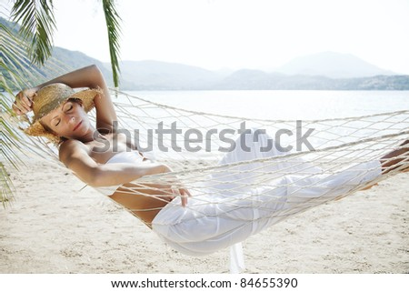closeup of young woman relaxing in a hammock by the beach