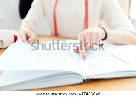 Closeup of young woman seamstress pointing and reading notes in notebook - stock photo