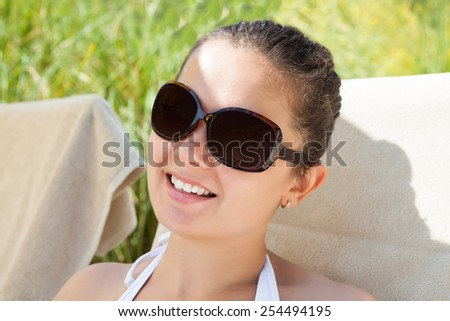 Closeup of young woman wearing sunglasses on sunny day at resort - stock photo