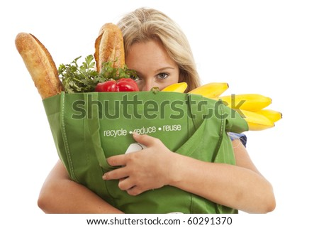 Closeup of young woman with green recycled grocery bag of healthy food and vegetables