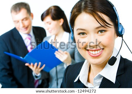 Closeup of young woman with headset looking at camera with smile in working environment
