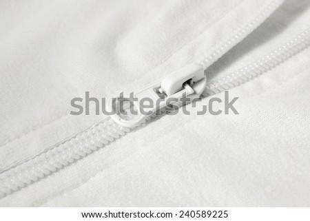 Closeup of zipper in white cloth, a horizontal picture - stock photo