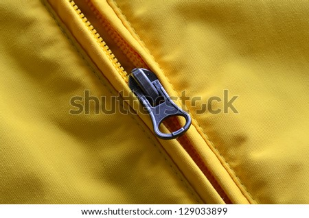 Closeup of zipper on Yellow coat with texture - stock photo