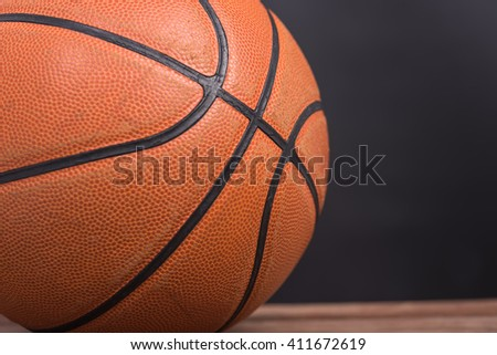 Closeup old basketball basket ball on wooden and black background