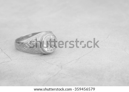Closeup old diamond ring on blurred cement floor background in black and white tone - stock photo