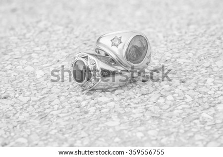 Closeup old diamond rings on blurred stone floor background in black and white tone - stock photo