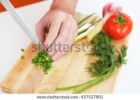 Closeup old man's hands cutting vegetables on a work surface in a kitchen. - stock photo