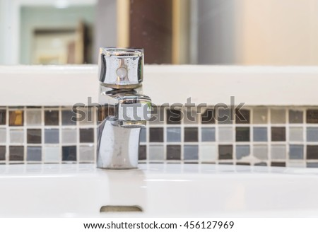 Closeup old stainless faucet in the toilet with interior of toilet view background - stock photo