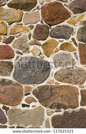 Closeup old stone wall. Vintage house outdoors in the sun. - stock photo