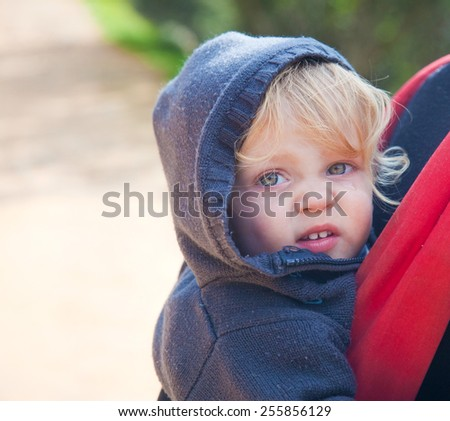 CLoseup on a blond baby in a backpack on a parent's back while outdoors - stock photo