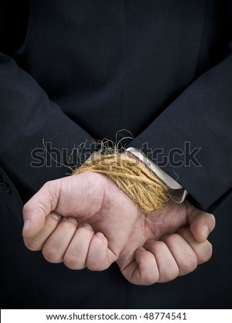 Closeup on a businessman's tied up hands.