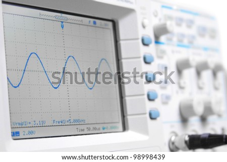 Closeup on a digital oscilloscope showing a sinusoidal waveform - stock photo