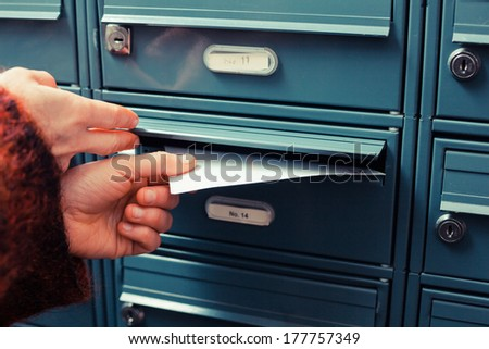 Closeup on a female hand putting a letter in a letterbox - stock photo