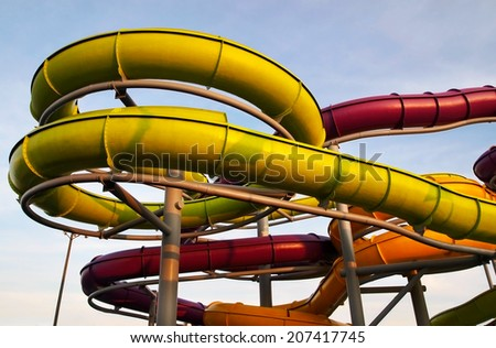 Closeup on a twisty, curly collection of multi-colored tubular slides at an outdoor water park. - stock photo