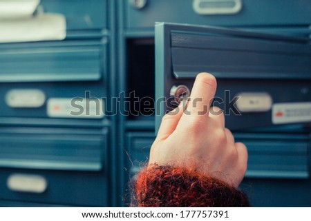 Closeup on a woman's hand as she is getting her post out of her letterbox - stock photo