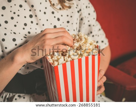 Closeup on a young woman eating popcorn in a movie theater - stock photo