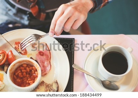 Closeup on a young woman's hands as she is having breakfast - stock photo