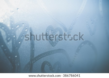 Closeup on abstract blurred love heart symbols drawn by hand on the wet frozen window glass sunlight background. Selective focus used. - stock photo