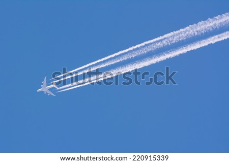 Closeup on airplane contrail against clear blue sky - stock photo