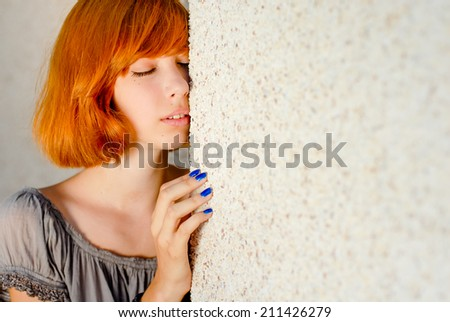 closeup on attractive romantic sensual pretty girl posing eyes closed near copy space gray wall background portrait  - stock photo