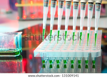 Closeup on automatic multipipette tips over 96 well plate for DNA amplification - stock photo