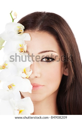 Closeup on beautiful face with white orchid flower, perfect clean skin, young female portrait,  isolated on white background with white text space, beauty and spa concept - stock photo